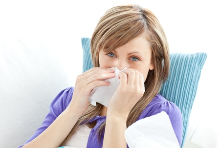 Portrait of a sick pretty woman blowing lying on a sofa against white background Stock Photo - 10249825