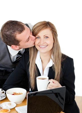 Young businessman kissing his delighted girlfriend photo