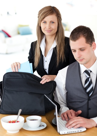 Businesswoman packing her bag businessman using laptop Stock Photo - 10248528
