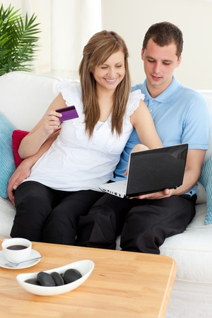 Happy couple using a laptop to buy online  photo