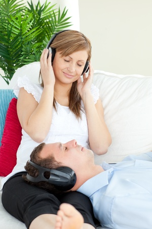 Cute woman listening to music with her boyfriend lying on a sofa  Stock Photo - 10247626
