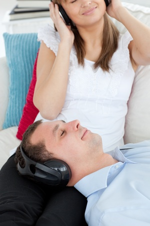 Close-up of a man listening to music lying on the sofa with his girlfriend Stock Photo - 10248673