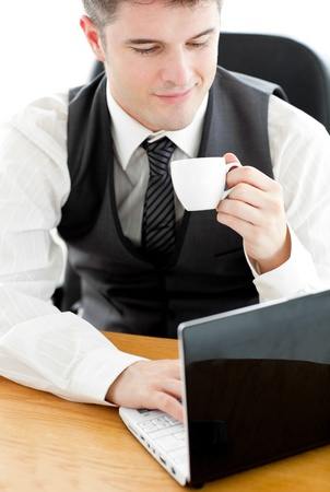 Happy young businessman looking at his laptop holding a coffee  sitting at his desk photo