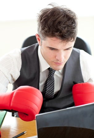 Ambitious businessman wearing boxing gloves in the office  Stock Photo - 10246616