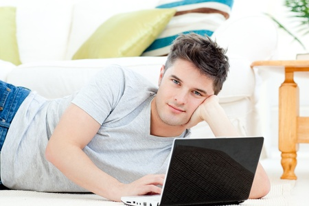 animated adult: Handsome young man lying on the floor with a laptop