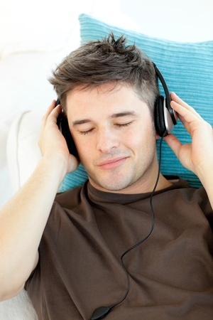 Attractive young man listening to music lying on a sofa Stock Photo - 10248751