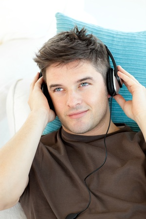 Smiling young man with headphones listening to music photo