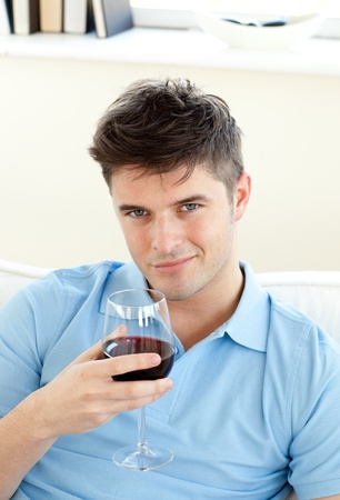 Handsome young man sitting on a sofa holding wineglass photo