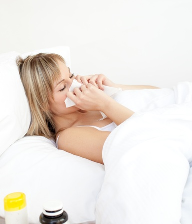 Sick woman blowing lying on a bed  photo