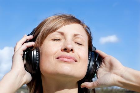 Beautiful woman listenng music outdoors photo