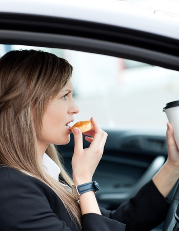 drinking and driving: Attractive businesswoman eating and holding a drinking cup while driving