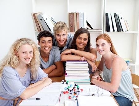 adolescentes estudiando: Adolescentes sonrientes estudiar Ciencias en una biblioteca