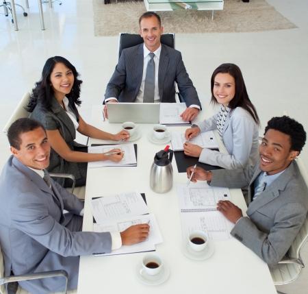 reunion de trabajo: Empresarios en una reuni�n sonriendo a la c�mara Foto de archivo