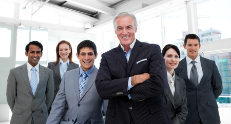 Senior manager with folded arms accompanied by his team Stock Photo - 10247513