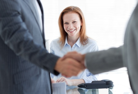 Businesswoman smiling with businessmen greeting each other in the foreground photo