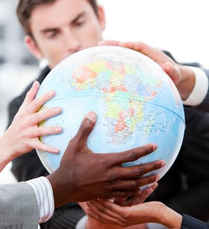 拡大: 地球儀を保持しているビジネス チームのクローズ アップ 写真素材