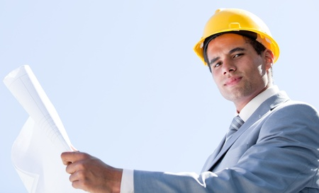 executive helmet: Smiling male architect holding a blueprint