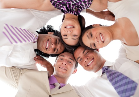 diverse people: Smiling business team in a circle with heads together Stock Photo