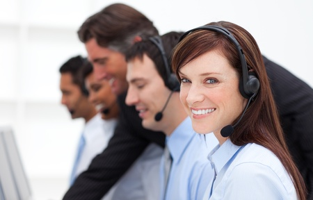 Pretty businesswoman and her team working in a call center Stock Photo - 10247687