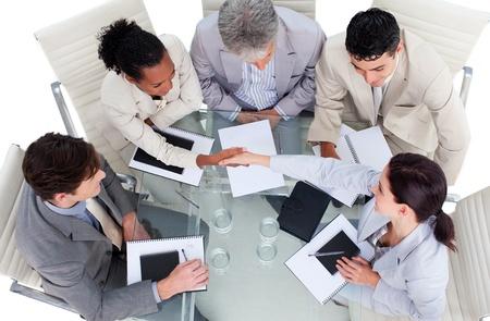 cerrando negocio: Equipo de negocios multi�tnica lindo cerrar un trato Foto de archivo