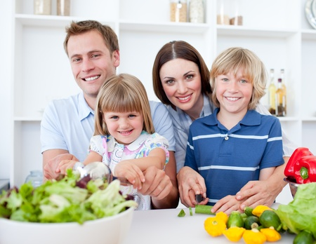 comidas saludables: Alegre joven familia cocina juntos