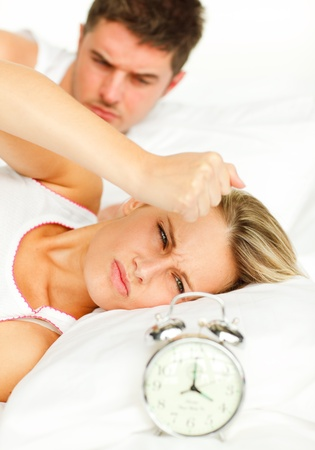 Man and angry woman in bed looking at the alarm clock going off photo