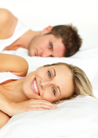 Couple resting in bed and woman smiling at the camera photo