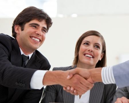 Glimlachend zakenman en zijn collega een deal sluiten met een partner