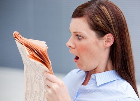 Astonished businesswoman reading newspaper photo