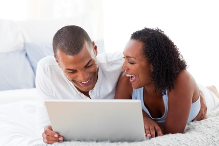 Happy couple using a laptop  photo