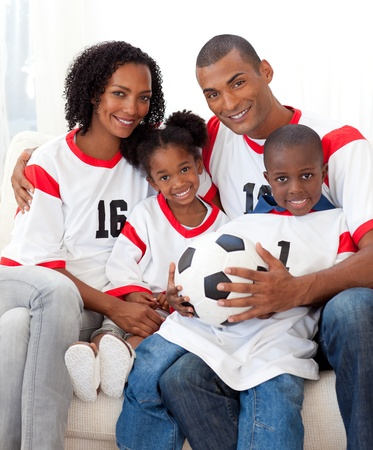 Smiling family holding a soccer ball photo