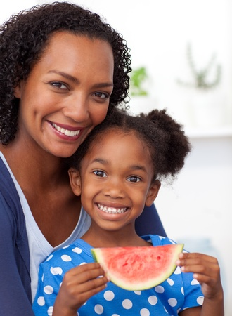 Smiling mother and her daughter eating fruit photo