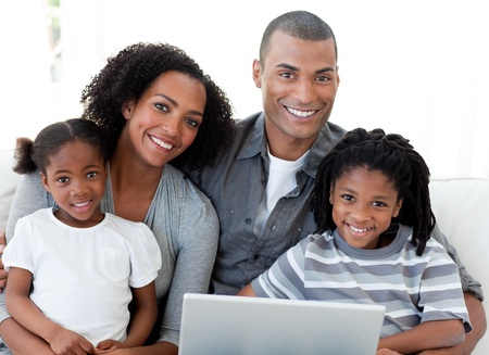 famille africaine: Heureuse la famille afro-américaine en utilisant un ordinateur portable dans le salon