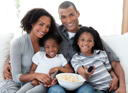 ethnic women: Afro-American family watching television at home