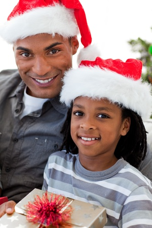 Portrait of an Afro-American father and son holding a Christmas gift photo