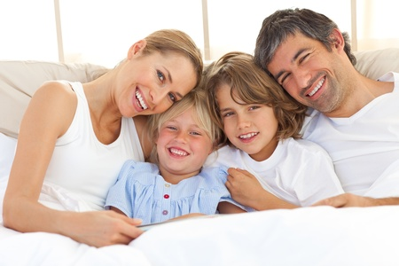 Happy family reading a book on bed photo