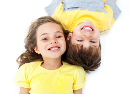 women children: Smiling siblings lying on the floor Stock Photo