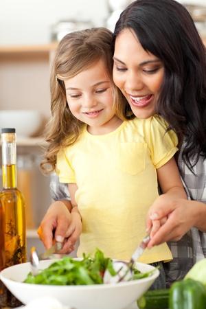 mama e hija: Madre Morena ayudando a su hija a preparar ensalada Foto de archivo