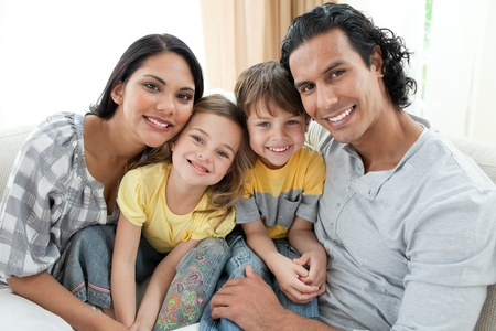 Portrait of a smiling family sitting on sofa Stock Photo - 10248890