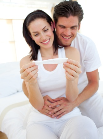prueba de embarazo: Pareja sonriente encontrar resultados de una prueba de embarazo