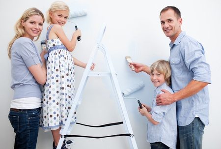 Lively family painting a wall in a new house photo