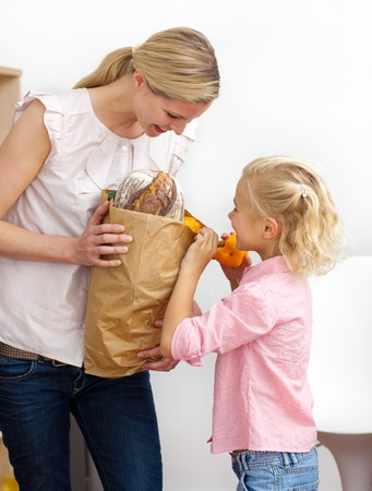 sustenance: Little girl unpacking grocery bag with her mother Stock Photo