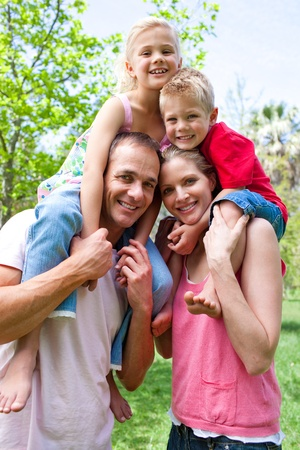 Happy parents giving their children piggy-back ride Stock Photo - 10250272