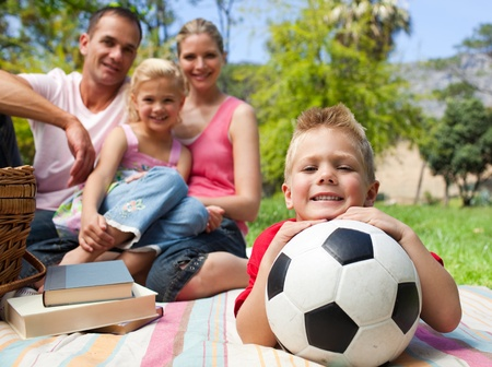 Little boy having fun with a soccer ball with his family smiling photo