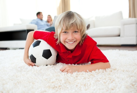 Smiling boy watching football match lying on the floor  photo