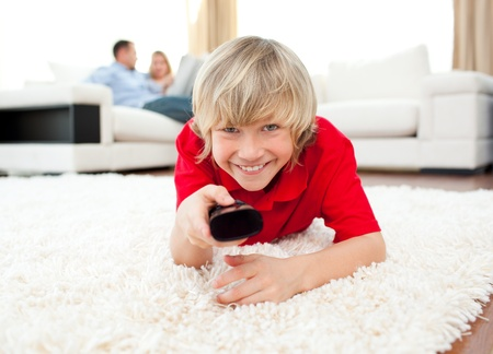 Happy boy holding a remote lying on the floor Stock Photo - 10246462