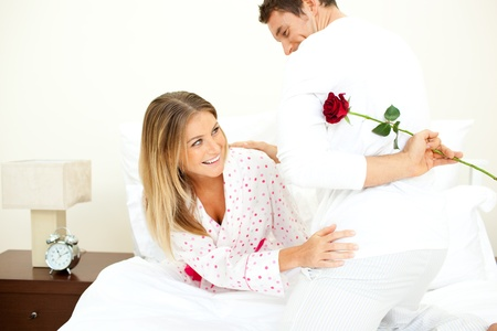 Attentive man giving a rose to his wife  Stock Photo - 10246219