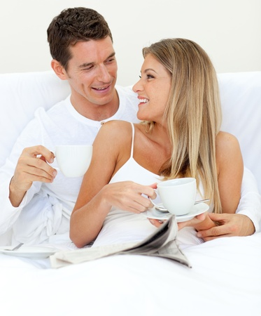 Enamored couple drinking a cup of tea lying on their bed photo