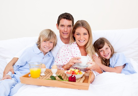 child in bed: Smiling family having breakfast sitting on bed