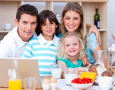 Joyful family using laptop during the breakfast photo